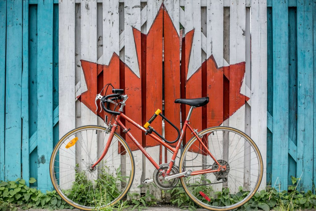 Bicycle positioned in from of wooden fence painted with Canadian maple leaf flag icon.