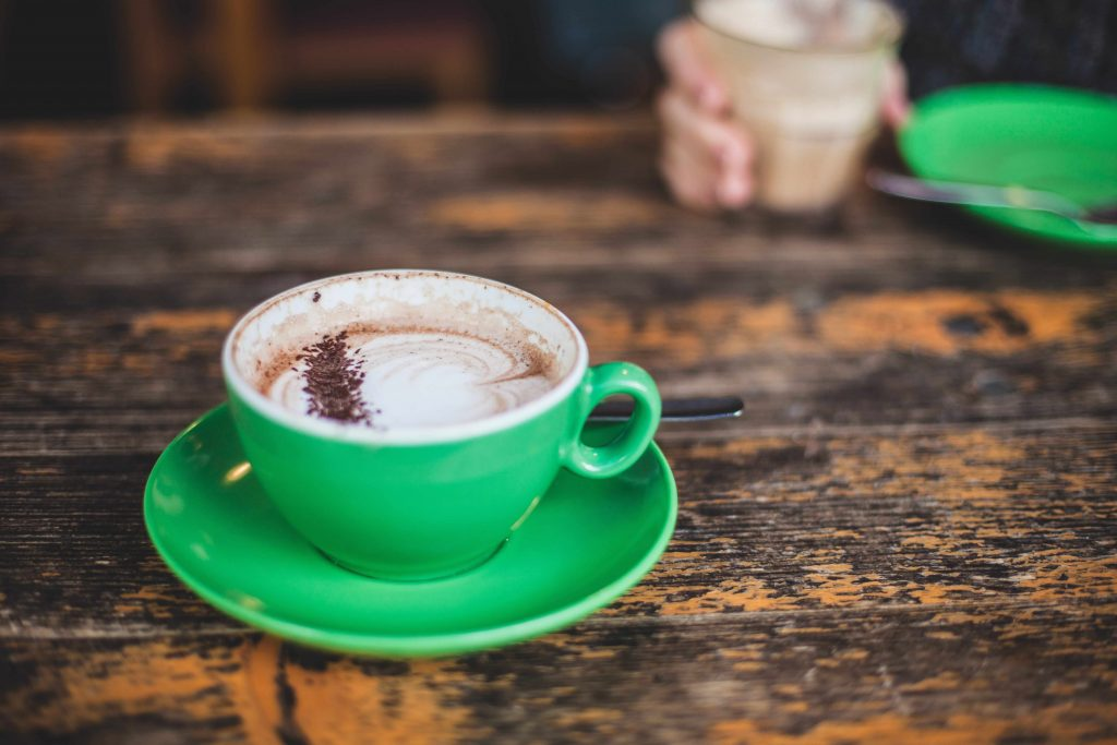 A cappuccino served in a green mug set upon a wooden table.