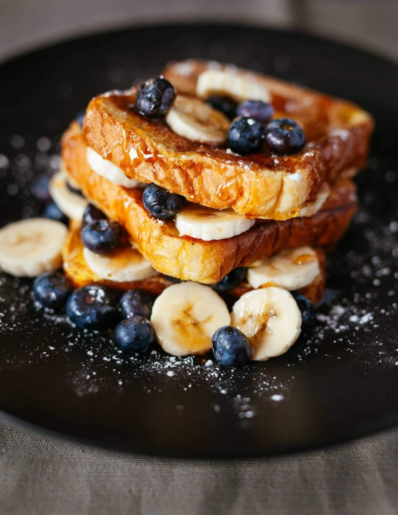 Stack of french toast layered with fresh bananas and blueberries dusted with confectioners sugar.