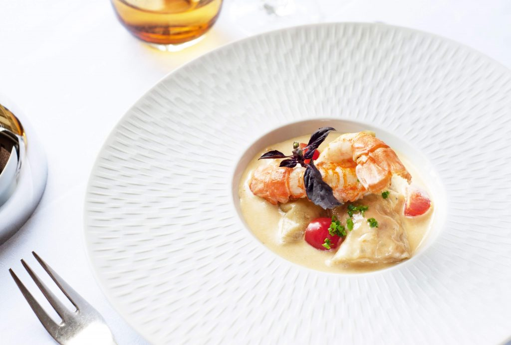 Delicious seafood in a rich cream sauce serve in a beautiful decorative white dish served at fine restaurant.