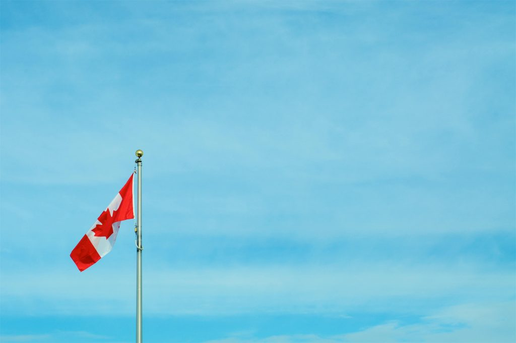 Flag pole with raised Canadian flag set in from of a blue sky backdrop.