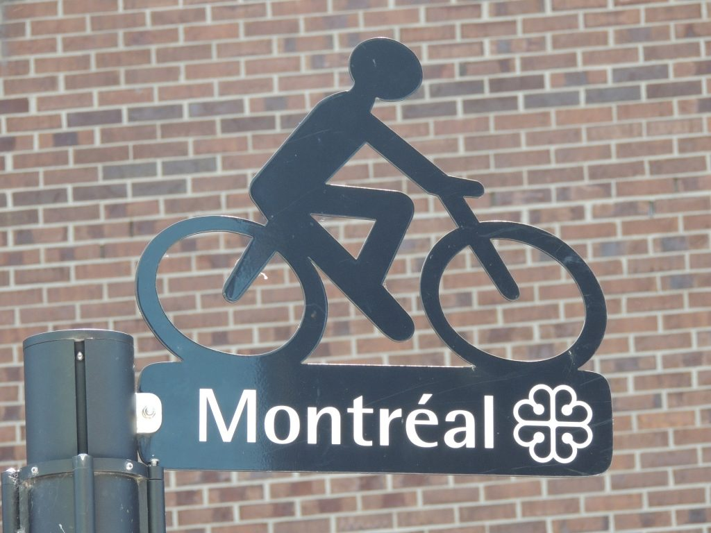 Street sign at intersection in Montréal Canada with a decorative cyclist on top.